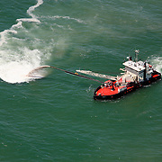 An aerial photo of a ship dredging an inlet near Carolina Beach, NC. Dredging pumps sand and sediment from the bottom of a shallow area to another location where it does not endanger boats and ships from running aground.