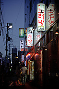 Tokyo, September 18 2011 - A couple walking on the street by night, with below illuminated signs written in Korean. Korean mania reached Tokyo's Korean neighborhood near Shinokubo station. For a long time Japanese ladies in their 50ies have been interested in Korean televised dramas. Recently the success of K-Pop (Korean popular music) in Japan has brought a younger population in the neighborhood.