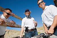 Men and woman with hand guns at firing range