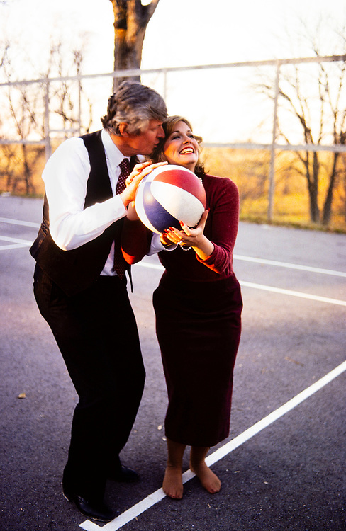 """Phyllis George and new husband, Kentucky governor elect John Y Brown play a game of """"horse"""" on a basketball court at their home in Lexington. Brown is trying to distract his new bride by kissing and blowing in her ear. Phyllis Ann George was an American businesswoman, actress, and sportscaster. She was also Miss Texas 1970, Miss America 1971, and the First Lady of Kentucky from 1979 to 1983. Ms. George died, aged 70, of complications from Polycythemia vera on May 14, 2020 in Lexington, Kentucky."""