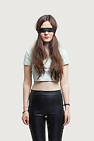 Young blindfolded woman standing against gray background