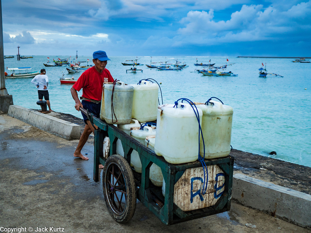 18 JULY 2016 - KUTA, BALI, INDONESIA: A worker in the fish market at Pasar Ikan pantai Kedonganan gets sea water from the ocean to pour over fish for sale in the market.    PHOTO BY JACK KURTZ