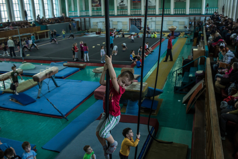 A young boy climbs a rope during gymnastics practice at the Shakhtar Palace of Sport on Wednesday, March 23, 2016 in Donetsk, Ukraine.