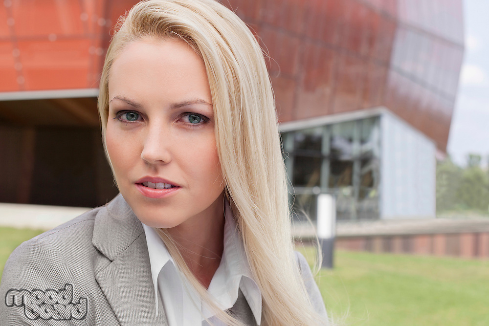 Close-up portrait of young businesswoman against office building