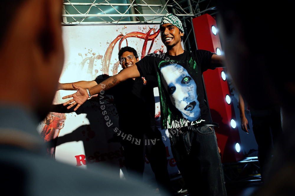 Young men are dancing on stage at a Coca Cola event organised at a McDonald's fast-food restaurant on Clifton Beach, a renowned costal area near the centre of Karachi, Pakistan's main economic hub.