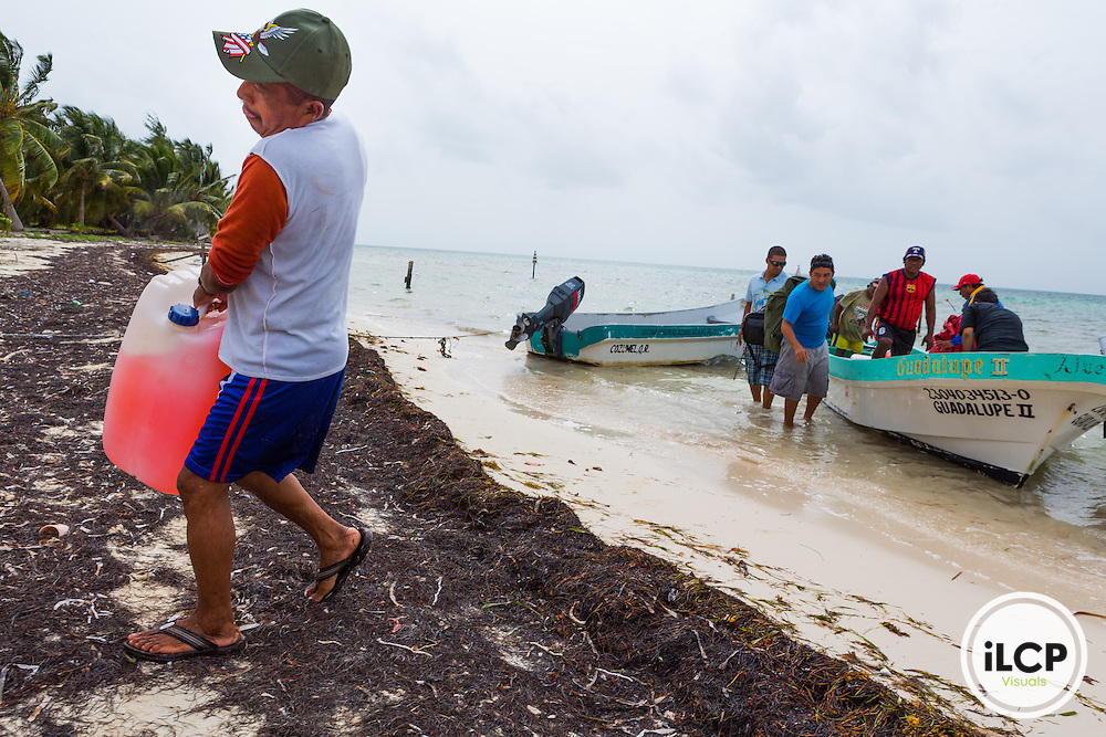 A fisherman unloading fuel in La Victoria, a small, remote fishing camp in the Sian Ka'an Biosphere Reserve in southernmost Caribbean Mexico. From a 2014 iLCP (International League of Conservation Photographers) expedition project documenting the people and places of the Mexican section of the Mesoamerican Reef (MAR).