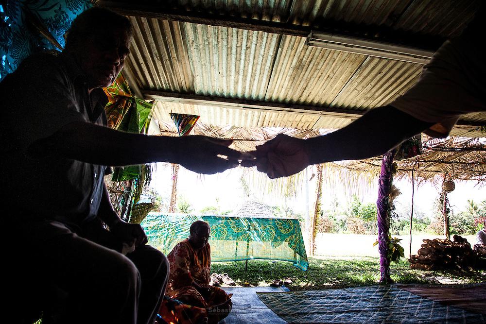 Lors des échanges coutumiers, l'argent circule de main en main depuis le porte-parole vers les ainés du clan. Chacun fait mine de le refuser pour qu'il soit attribué à un autre. Lorsqu'il est accepté par une personne, l'argent sera quoi qu'il en soit redistribué. Lorsque l'argent est donné en coutume, il semble ne plus avoir de valeur vénale, mais il devient le symbole de la transmission de la Parole.<br /> Cérémonie coutumière de mariage – Huiwatrul, Grande chefferie de Lössi, Lifou - Îles Loyauté, Nouvelle-Calédonie - Avril 2014