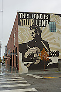 A person walks toward a mural of Woody Guthrie outside the Woody Guthrie Center in the Brady District on Friday, October 18, 2013, in Tulsa, Oklahoma.<br /> <br /> http://www.thebradyartsdistrict.com/<br /> http://woodyguthriecenter.org/