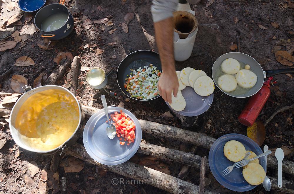 """AUYANTEPUY, VENEZUELA. Guía preparando arepas para el  desayuno en el campamento ''campo lecho''. El Auyantepuy es el mayor de los tepuis del Parque Nacional Canaima. En sus 700 kms2 alberga el salto angel o conocido por lengua indígena Pemon como """"Kerepacupai Vena; es la caída de agua más grande del mundo con sus 979 metros de altura. (Ramon lepage /Orinoquiaphoto/LatinContent/Getty Images)"""