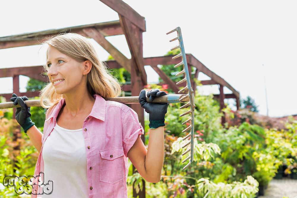 Portrait of smiling mature beautiful gardener holding fork rake