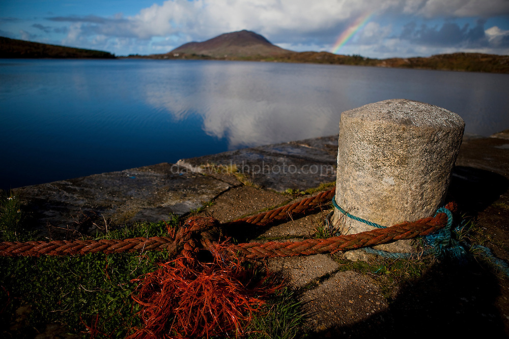 Granite Bollard on the quay in Ballinakill harbour, Connemara, Galway. Rainbow in the background.