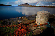 Granite Bollard on the quay in Ballinakill harbour, Connemara, Galway. Rainbow in the background.