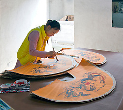 A woman paints a large Chinese fan in a craft workshop, Yangshuo hutong, Southern China.