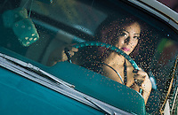Young woman driving classic car in the rain. Focus on water drops.