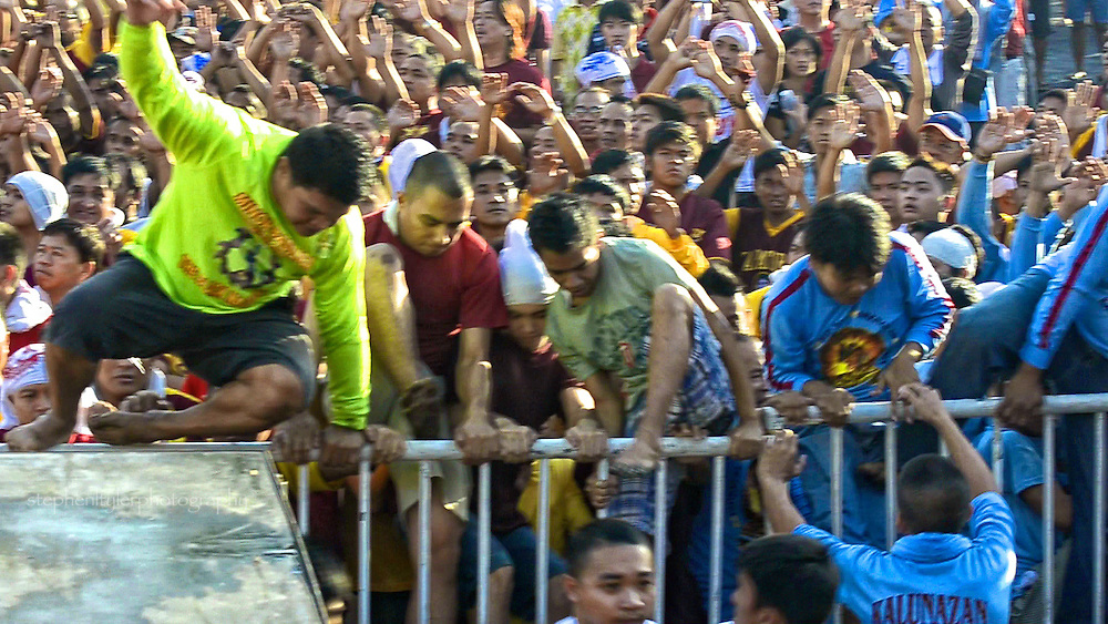 Devotees storm the fence in attempt to reach the stage where the carriage holding the statue and cross of the Black Nazarene awaits the start of the procession.
