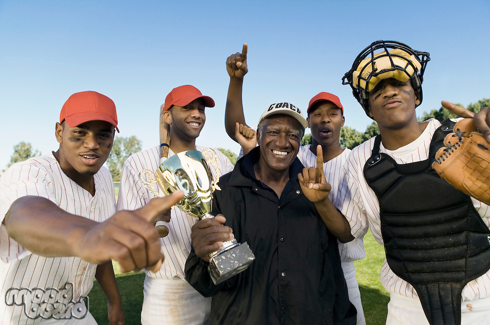 Baseball team and coach celebrating victory outdoors (portrait)