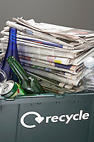 Recycling bin filled with waste paper and bottles close-up