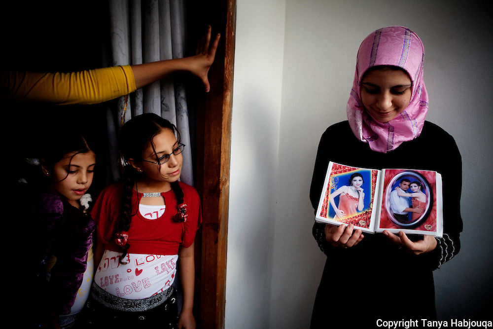 In the Gaza City home of Dr Jamal Shareef, a literature professor at Al Azhar University, his 16-year-old niece (R) shows pictures of her fiancé [Tanya Habjouqa]