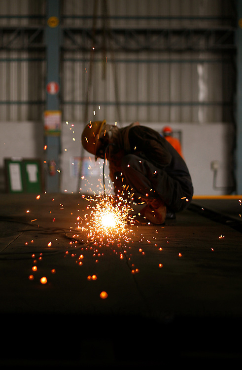 A workman grinds metal plates at a shop in the Ship Building Yard of Larsen and Tubro Ltd in Hajira, India, on Tuesday, October 9, 2007. Photographer:  Prashanth Vishwanathan/Bloomberg News