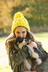 Teenage Girl Hugging Puppy Outdoors