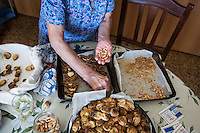 ACCIAROLI (POLLICA), ITALY - 5 OCTOBER 2016: 82-years old Fenisia La Greca prepares sun-dried figs stuffed with lemon zest, almonds and cinnamon, here in her kitchen in Acciaroli, a hamlet in the municipality of Pollica, Italy, on October 5th 2016. Fenisia La Greca grows fruit and vegetables in her own garden.<br /> <br /> To understand how people can live longer throughout the world, researchers at University of California, San Diego School of Medicine have teamed up with colleagues at University of Rome La Sapienza to study a group of 300 citizens, all over 100 years old, living in Acciaroli (Pollica), a remote Italian village nestled between the ocean and mountains in Cilento, southern Italy.<br /> <br /> About 1-in-60 of the area's inhabitants are older than 90, according to the researchers. Such a concentration rivals that of other so-called blue zones, like Sardinia and Okinawa, which have unusually large percentages of very old people. In the 2010 census, about 1-in-163 Americans were 90 or older.