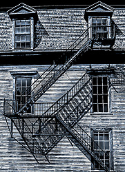 A fire escape offers some reassurance attached to an elderly building. The escape and its shadow cast a pattern on the building wall.