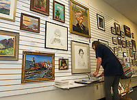 Abby Green visiting from Virginia looks through artwork at Lakes Region Art Association's gallery space in the Tanger Outlet on Friday afternoon.  (Karen Bobotas/for the Laconia Daily Sun)