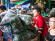 17 MAY 2013 - BANGKOK, THAILAND: A vendor packs chilies onto a handtruck in the flower market in Bangkok. The Bangkok Flower Market (Pak Klong Talad) is the biggest wholesale and retail fresh flower market in Bangkok. It is also one of the largest fresh fruit and produce markets in the city. The market is located in the old part of the city, south of Wat Po (Temple of the Reclining Buddha) and the Grand Palace.   PHOTO BY JACK KURTZ