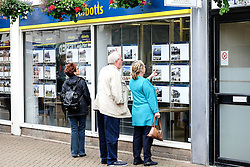 People looking into an estate agents window.