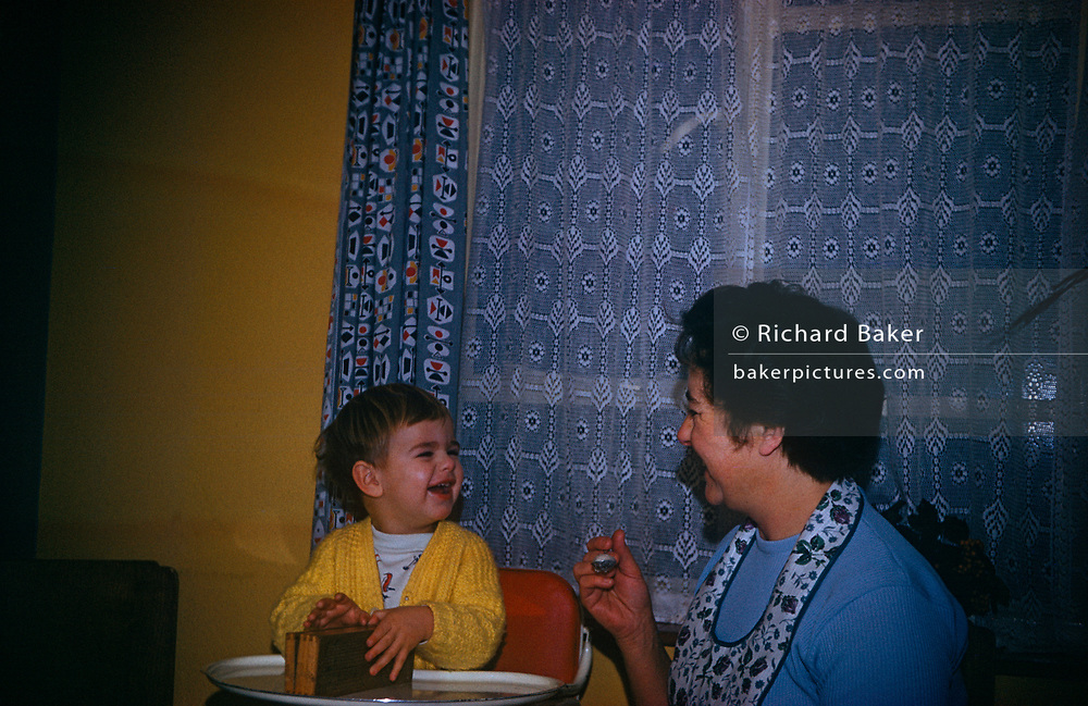 A 1960s lady spoon feeds a young one year-old son, during an evening meal time in the family home, in March 1961, in Westcliff, Southend, Essex, England.