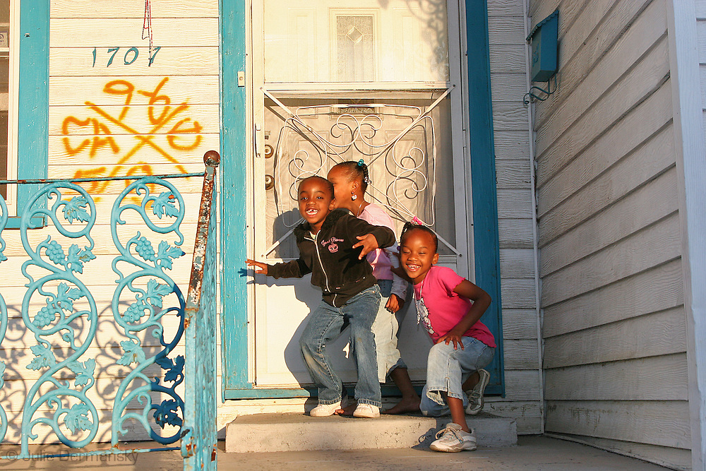 Children playing in front of a home marked by emergency workers following Hurricane Katrina in New Orleans