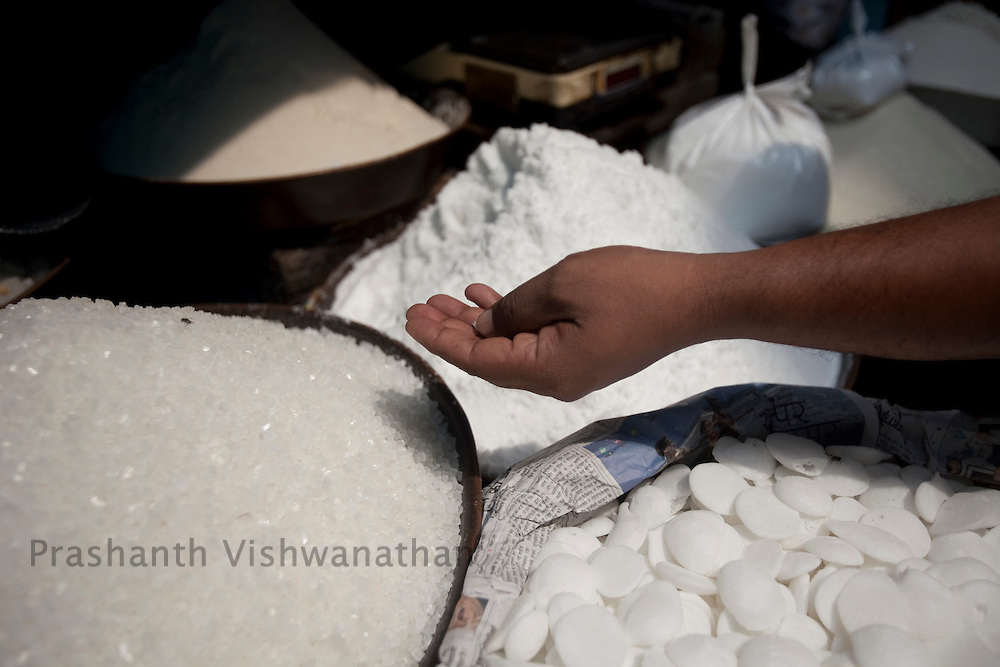 A customer checks the quality of sugar, at a wholesale market in Old Delhi, in New Delhi, India, on Wednesday September 2, 2010. Photographer: Prashanth Vishwanathan/Bloomberg News