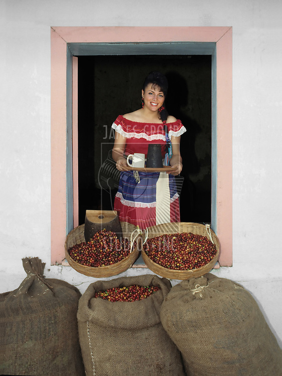 Woman in traditional Central American dress in an open window holding a tray with a coffee cup and a coffee pot while standing behind burlap bags of raw coffee beans