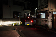 car driving through an old residential neighborhood at night Japan