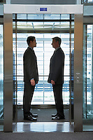 Businessmen standing face to face in elevator