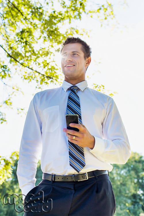 Low angle view of handsome mature businessman using smartphone