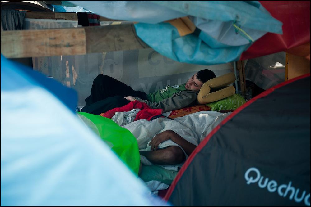 """Des manifestants se reposent sous des baches dans le camp place Puerta Del Sol. // Le mouvement spontane du """"15 M"""" (15 mai) compose de citoyens espagnols campe depuis 2 semaines sur la place Puerta Del Sol avec pour revendication la construction d'une democratie nouvelle. Organise en commission les citoyens prennent la parole lors d'assemblee ouverte a tous - Place Puerta Del Sol à Madrid le Juin 2011. ©Benjamin Girette/IP3Press"""