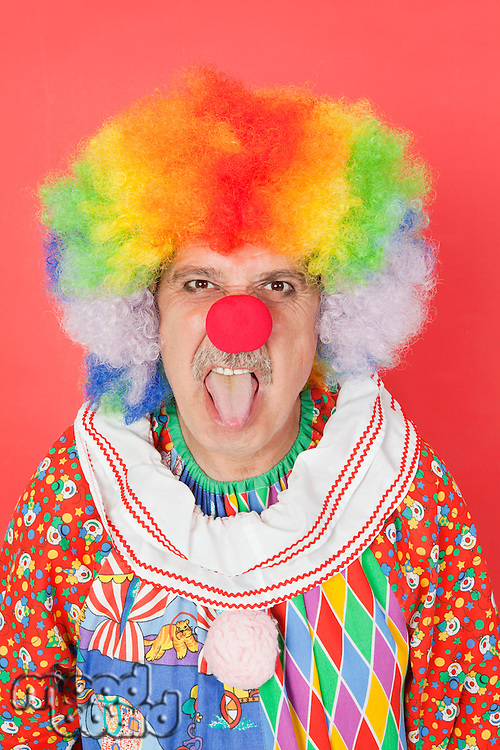 Portrait of senior male clown sticking out tongue over red background