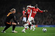 Emmanuel Eboue of Arsenal  goes past Philippe Mexes of AS Roma during the UEFA Champions League First knockout round, First Leg match between Arsenal and A.S. Roma at Emirates Stadium on February 24, 2009 in London, England