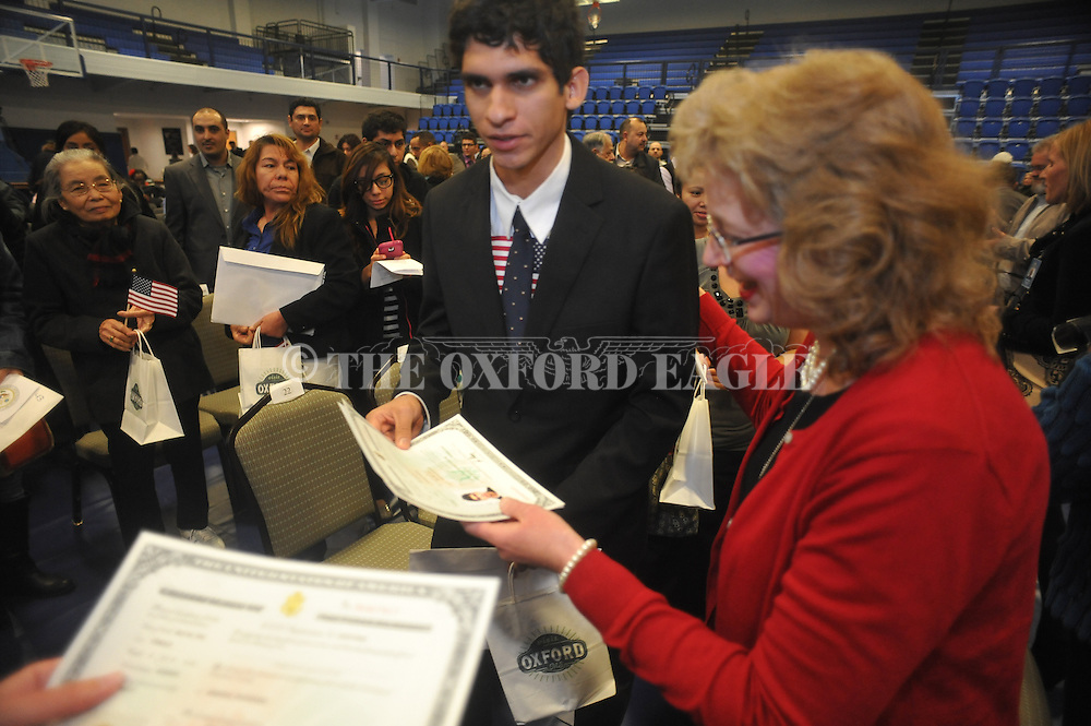 Sean Acosta of Starkville, Miss. receives his citizenship papers following a Naturalization Ceremony in U.S. District Court for the Northern District of Mississippi, at Oxford High School in Oxford, Miss. on Tuesday, November 18, 2014. The ceremony was the first the court has ever held at the school.