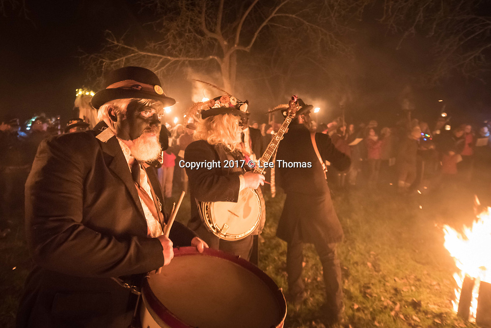 Much Marcle, Herefordshire, UK. 6th January 2018. Pictured:  Musicians of the Silurian morris side accompany the wassail cremony in the orchard. / Hundreds of people both young and old gathered at the Westons Cider Mill and adjoining orchard to take part in the traditional Wassail ceremony. The event at Much Marcle in Herefordshire was attended by the Silurian morris side who entertained the crowd with witty repartee, raucous dancing and music. According to their website, the true origins of blackened faces are lost to history, but are widely believed to be simply a form of disguise, possibly to overcome the oppressive anti-begging laws of the 17th century, and the eternal embarrassment of being a morris man. The orchard-visiting wassail refers to the ancient custom of visiting orchards in cider-producing regions of England, reciting incantations and singing to the trees to promote a good harvest for the coming year  // Lee Thomas, Tel. 07784142973. Email: leepthomas@gmail.com  www.leept.co.uk (0000635435)