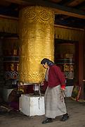 Woman spinning prayer wheel inside Memorial Chorten, Thimpu, Bhutan