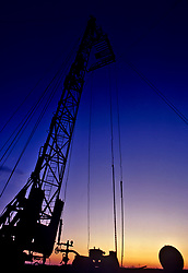 Stock photo of the silhouette of an on-shore drilling rig at sunset