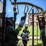 WASHINGTON, DC -JUL22: Erik Beard, 23,  who works at Beautiful U summer camp in Southeast, Washington, DC, through DC's Student Youth Employment Program, SYEP, helps Jah'Arah Edwards, 2, climb the monkey bars, July 22, 2015. (Photo by Evelyn Hockstein/For The Washington Post)