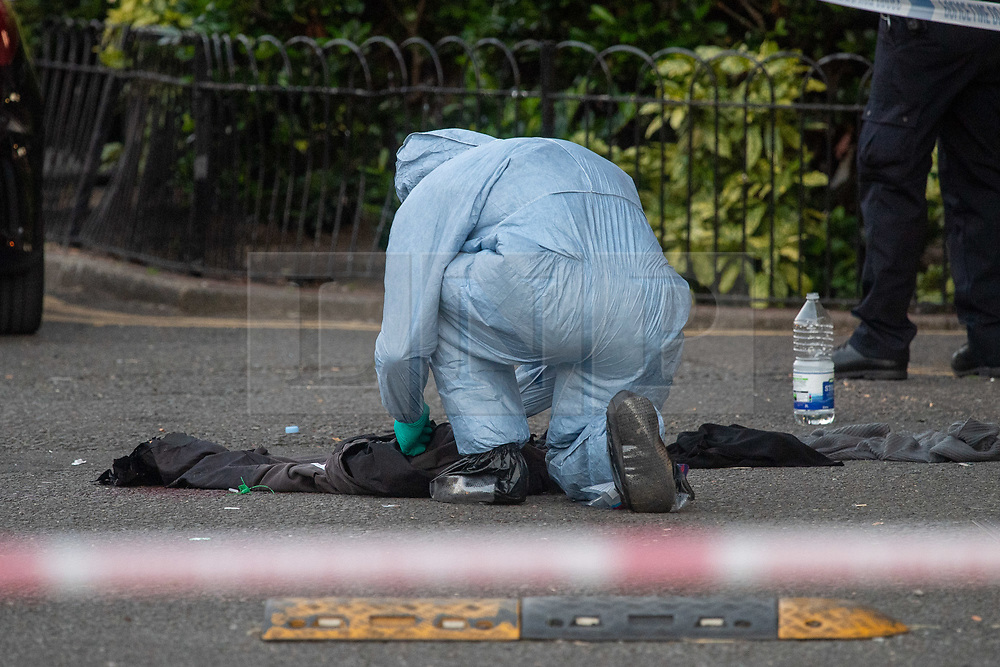 © Licensed to London News Pictures. 20/07/2020. London, UK. A forensic investigator looks over clothes next to a pool of blood at the crime scene as police launch investigation after two people were stabbed in Tower Hamlets. Photo credit: Peter Manning/LNP