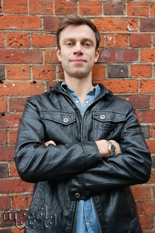 Portrait of man in leather jacket standing against brick wall