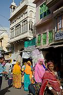 Women dressed in colourful saris walking through Pushkar, Rajasthan, India