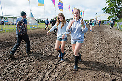 © Licensed to London News Pictures. 13/06/2015. Isle of Wight, UK.  Wellie clad festival goers battle through muddy conditions at Isle of Wight Festival 2015 on the morning of Saturday Day 3.  Yesterday suffered torrential rain all afternoon and evening, after a first day of warm sun.  This years festival include headline artists the Prodigy, Blur and Fleetwood Mac.  Photo credit : Richard Isaac/LNP