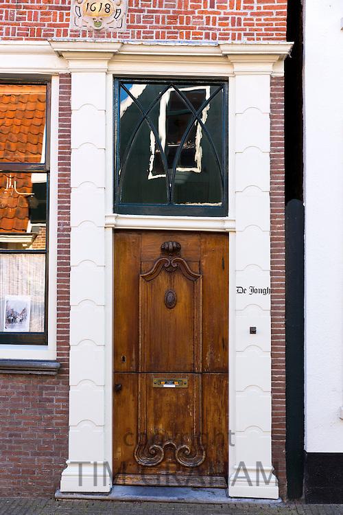 Quaint traditional wooden brown front door entrance doorway in the town of Edam, The Netherlands