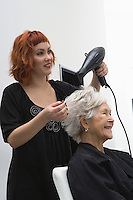 Stylist blow-drys elderly woman's hair